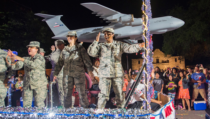 Airmen with the 433rd Airlift Wing wave to the grandstands as they pass in front of the Alamo during the Fiesta Flambeau parade April 23, 2016. The Fiesta Flambeau parade is one of the largest illuminated parades in the world, with over 750,000 spectators and 1.5 million television viewers. (U.S. Air Force photo by Benjamin Faske)